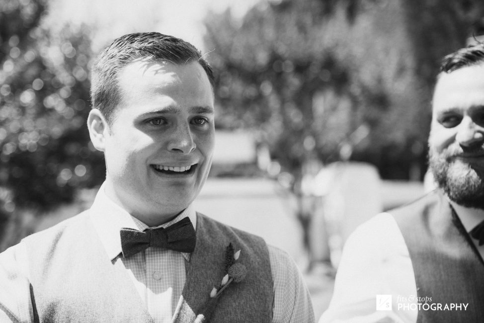 Photograph of a young caucasian groom tearing up at the sight of his bride during their wedding ceremony.