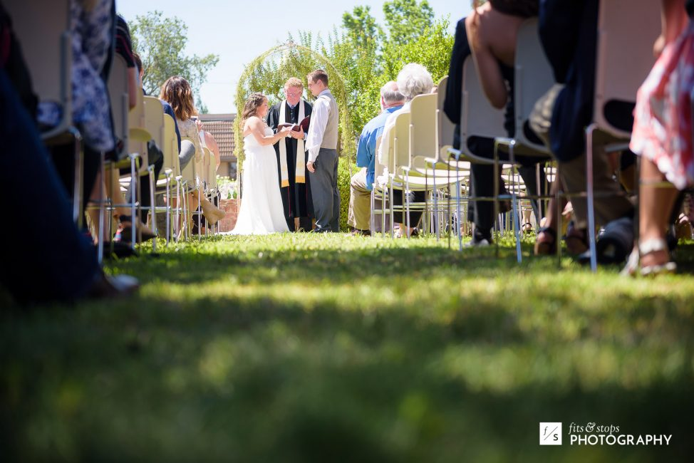 Photograph of a crowd looking on at a young man and woman getting married.