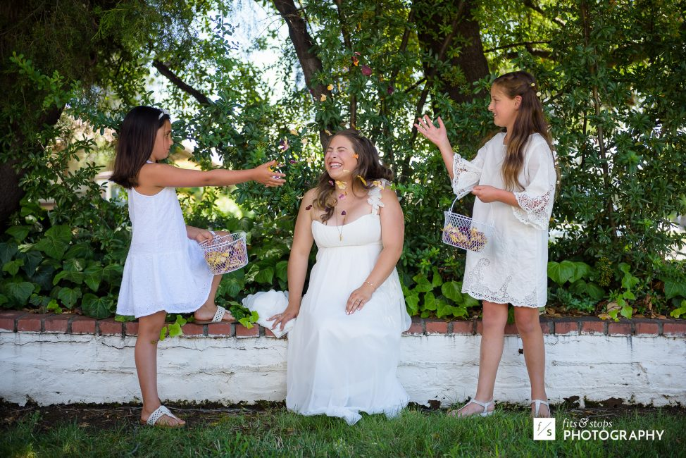 Photograph of two young flower girls tossing their petals over the bride.