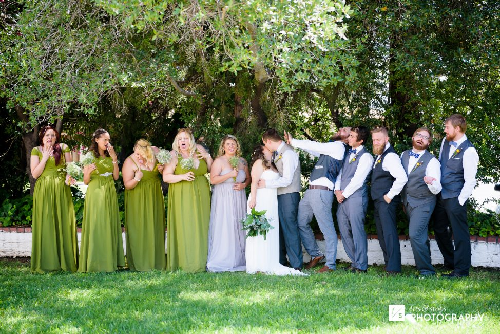 Funny photograph of a bridal party reacting with mock disgust to a bride and groom kissing.