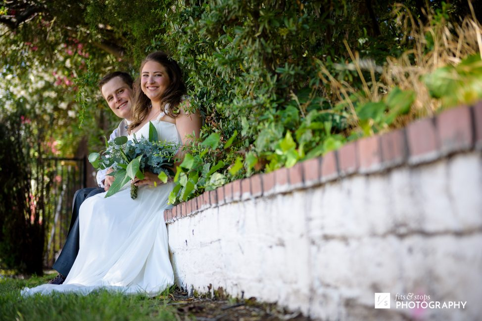 Photograph of a bride and groom sitting alone on a mission style brick wall.