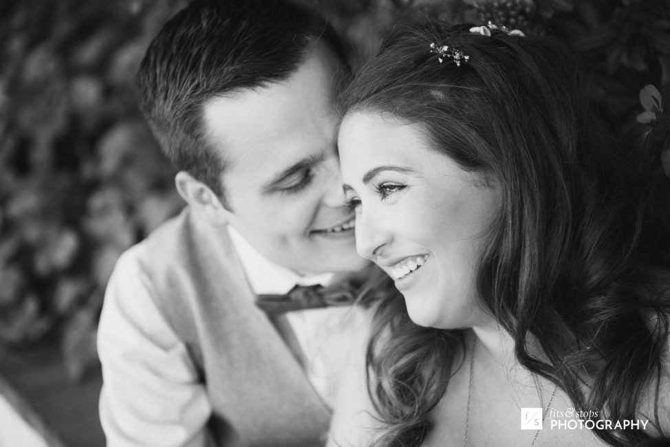 Black and white photograph of a groom causing his bride to smile with glee.