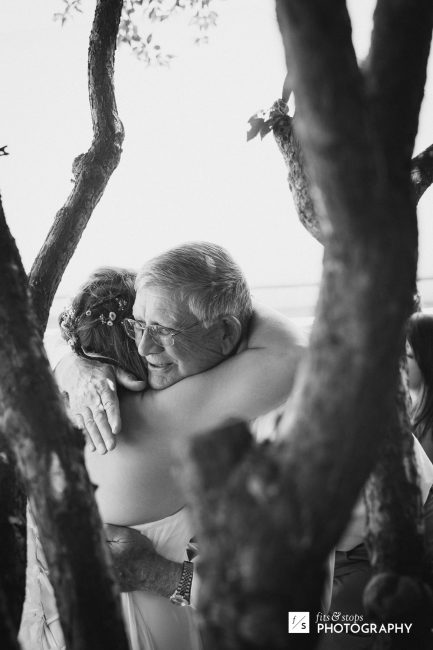 Black and white photograph of an old man hugging the bride.