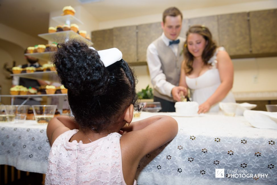 Photograph of a young girl watching closely as a bride and groom cut their wedding cake.