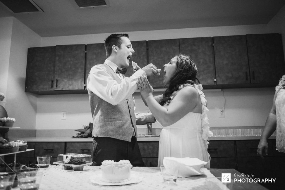 A black and white photograph of a young bride and groom feeding eachother a first bite of wedding cake.