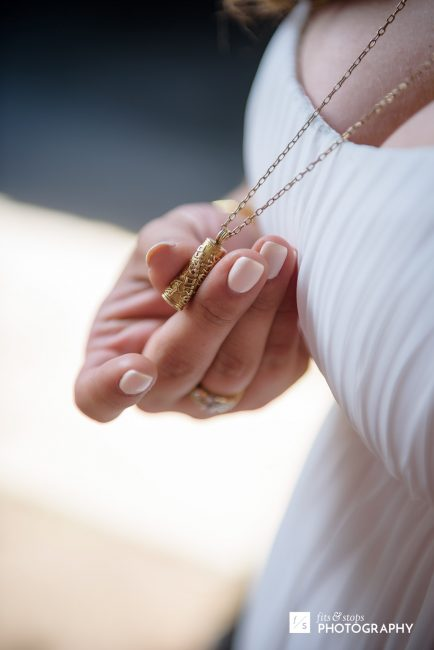 Photograph of a bride clutching her mezuzah necklace.