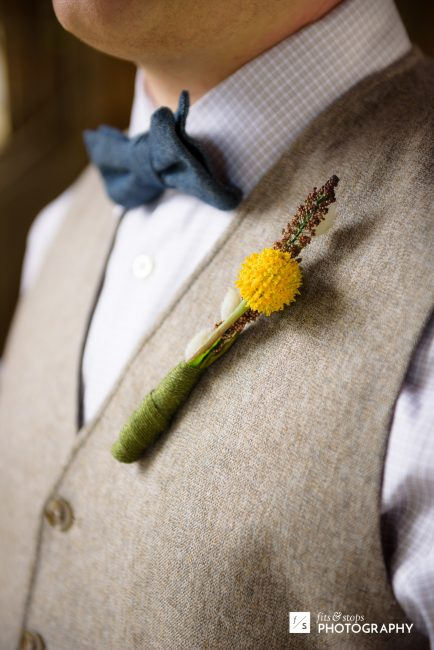 Close up photograph of a groom wearing his boutonniere.