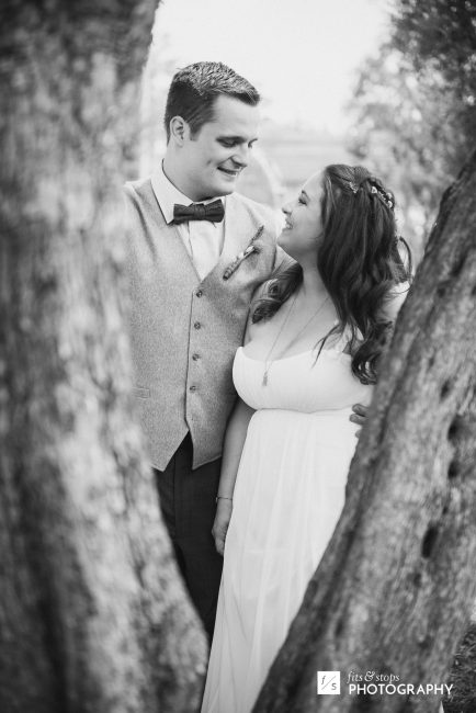 Black and white photograph of a bride and groom, framed by the branches of an olive tree.