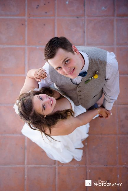 An overhead photograph of a young married couple against a red tile floor of a church buidling.