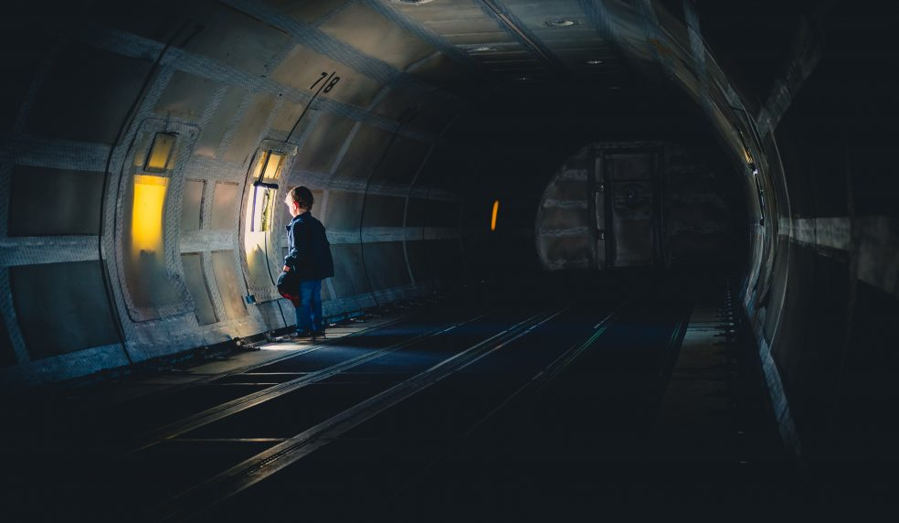 A photography of a young boy clutching his baseball cap as he looks out the only window in an empty cargo plan fuselage.