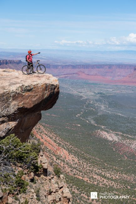 Photograph of a single mountain biker standing on a precipice on the Upper Porcupine Singletrack (UPS) section of the trail.
