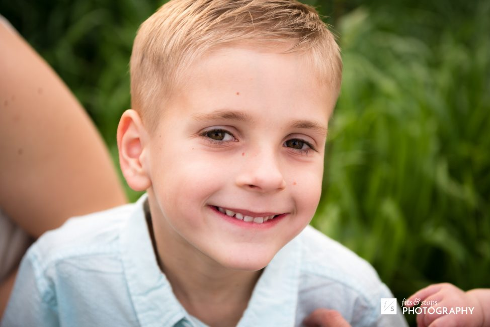 A portrait of a young boy with a shallow depth of field, in front of a grassy backdrop