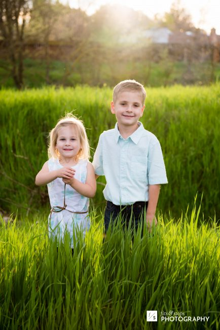 A little girl and her brother stop to pose for a portrait photo in a grassy field at sunset.