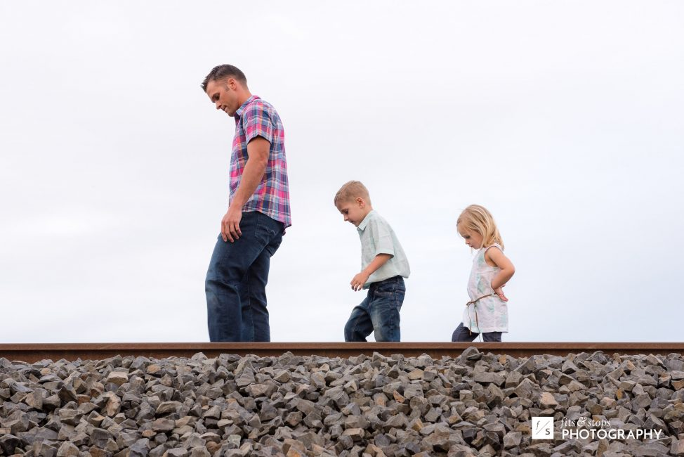 A father, his son and daughter walk along a railroad track in profile