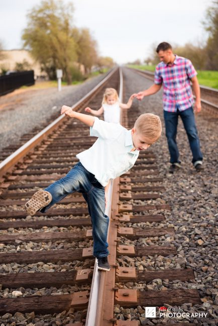 Photo of a young boy balancing on a railroad track rail