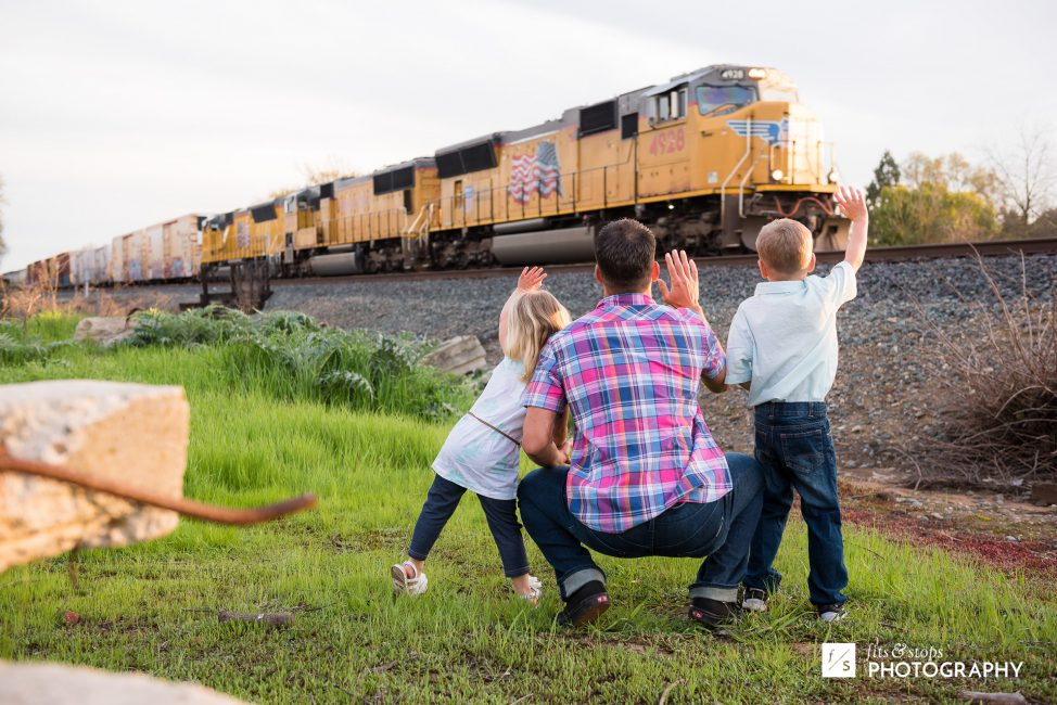 A father and his two young children wave at a passing train engine