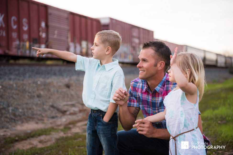 A father and his two young children wave and point at a passing train.