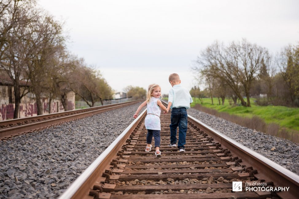 A young girl and her brother run down some railroad tracks, as she looks back toward the camera.