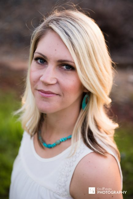 Portrait of a young blond woman wearing teal jewelry