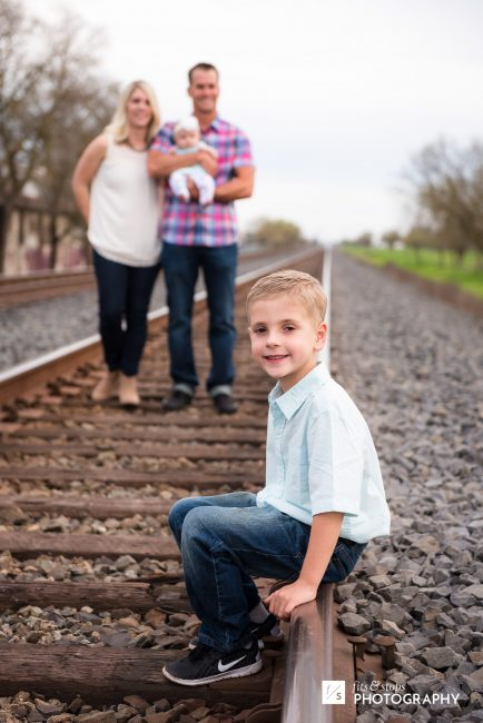 A little boy sits on a railroad rail while his family stands out of focus on the tracks.