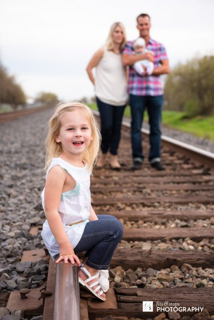 A little girl sits on a railroad rail while her family stands out of focus on the tracks.