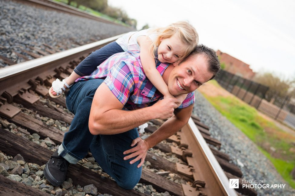 A little girl hangs on to the back of her father while they pose for a portrait in front of railroad tracks.